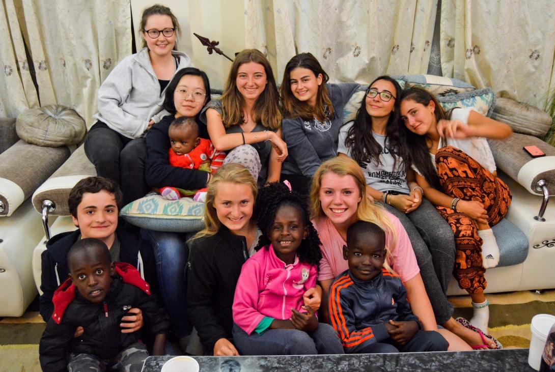 High School Special volunteers sitting in the living room with their host family's children in Kenya